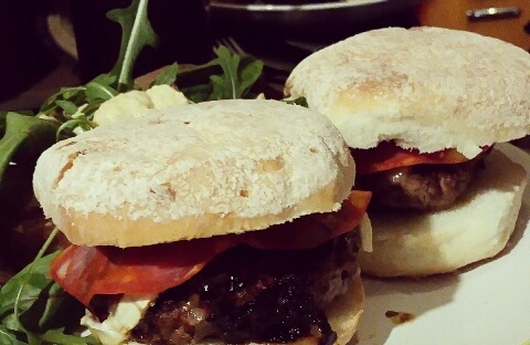 Gluten Free Home made Beef Burgers in large white Juvela White Rolls in the burgers is a some chorizo and a large side salad there is a lidded mason jar in the background with cola inside.