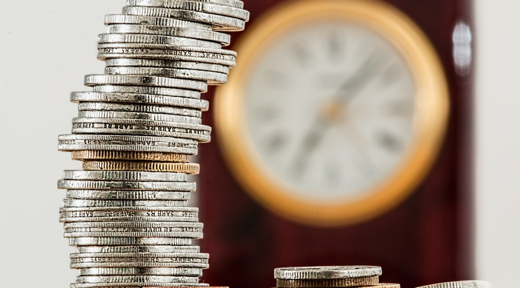 A photo of a stack of silver coins with a yellow rimmed clock in the background