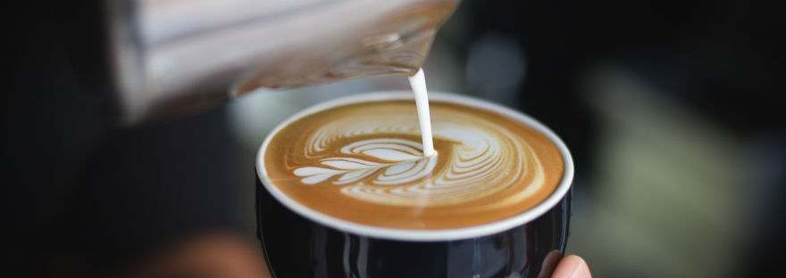 A barista artfully making 3 hearts with milk pouring in coffee.