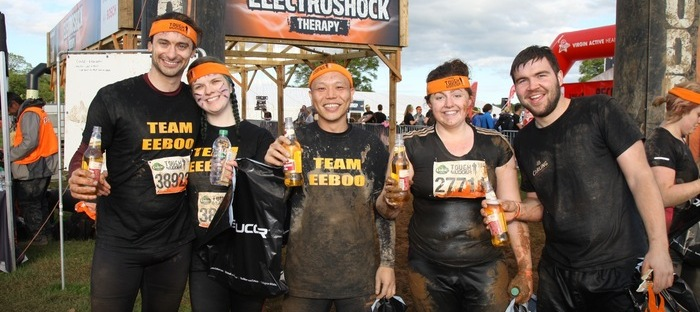 A photo of James, Lisa, Tony and 2 others drinking something out of bottles. They are all looking happy and relieved. They are all wearing black sportswear.
