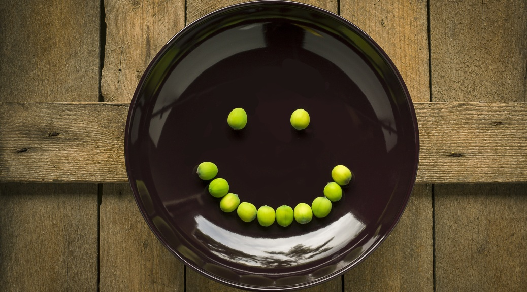 A camera down shot of a brown plate on a rough wood surface with a smiley face made of peas on the plate