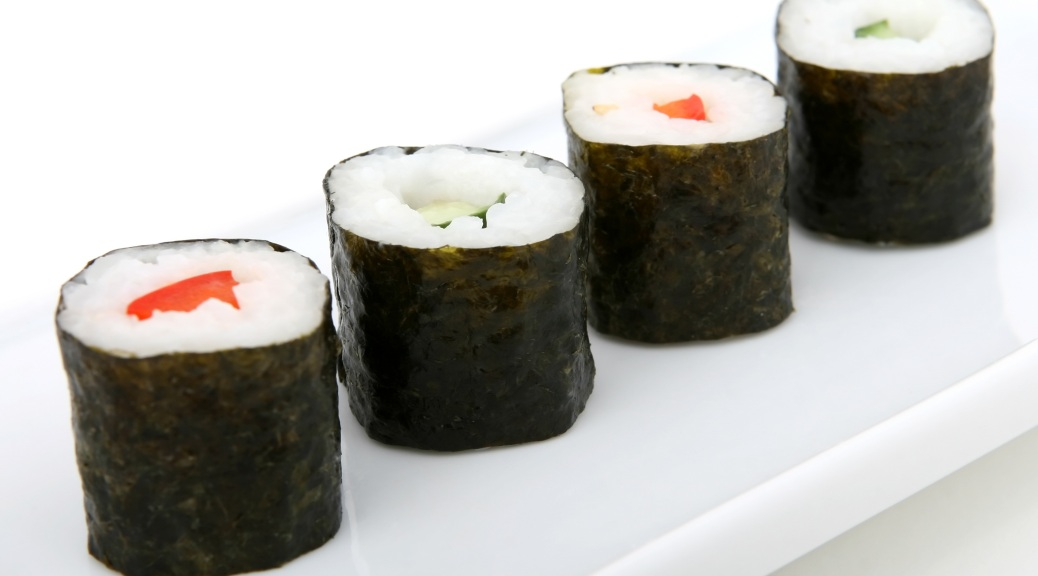 4 pieces of sushi on a white background - they are seaweed rolls with alternating pepper and cucumber filling