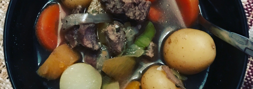 A camera down shot of beef stew in a black bowl sitting on a beige and burgundy knitted blanket