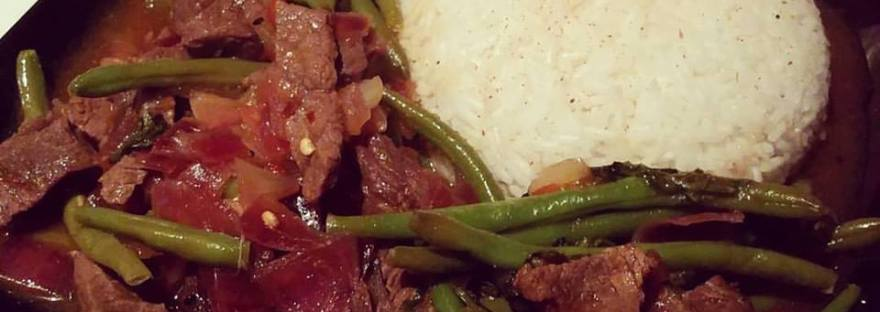 On a square black plate, there is a half-sphere of white sticky rice alongside a portion of beef and green beans ( chilli beef and bean)