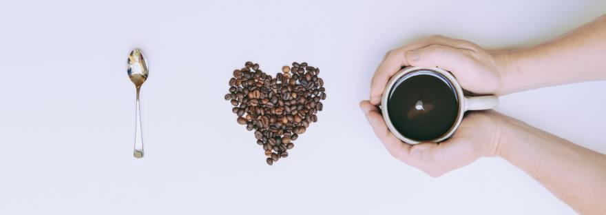 "Camera Down view of a blank white canvas with: A shiny silver spoon in a vertical axis signifying the letter ""I"" Coffee beans in the shape of a heart to be the word ""love"" Last is two hands entering the frame from the right surrounding a white cup with black coffee within."