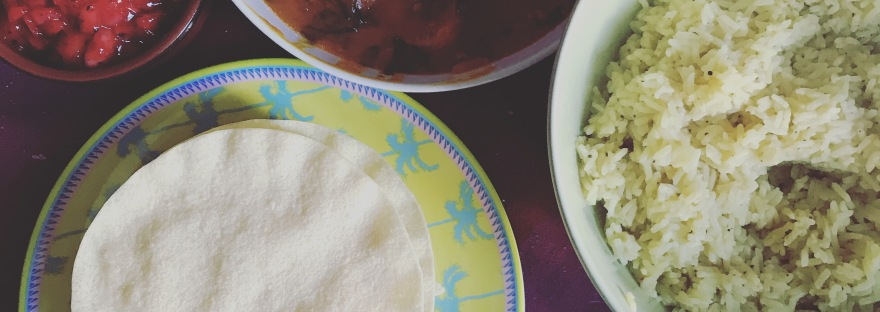 Downwards shot of a table with a pink cover. It has poppadoms on a plate with a palm tree print, rice & curry both in green bowls and a container spiced onions.